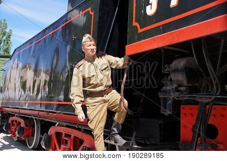 Fighter of Red Army in the form of times of World War II on a footboard of the old engine