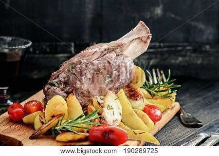 Pork knuckle baked with potatoes on a wooden board. Italian cuisine. Selective focus.