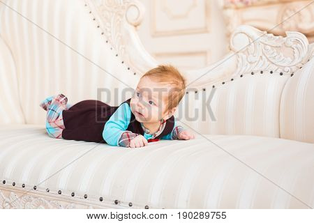 A portrait of a cute newborn baby lying on its stomach and smiling.