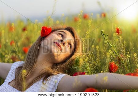 Woman in white dress relaxing in a full field of poppies