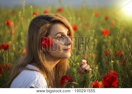 Woman in white dress dreaming among the full field of poppies
