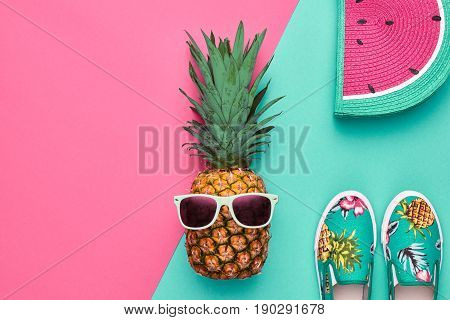 Fashion Hipster Pineapple Fruit. Bright Summer Color, Accessories. Tropical pineapple with Sunglasses, Stylish Handbag Creative Art concept. Minimal style. Pink blue summer party background