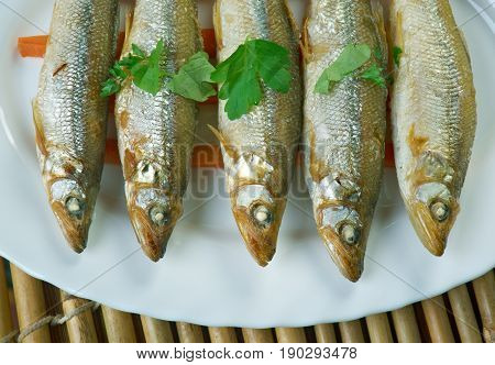 baked smelt served with roasted carrots.  close up.