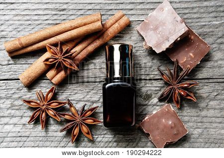 Chocolate skin treatment on wooden background. Cosmetic jar with lotion, cocoa, anise, cinnamon sticks, chocolate. Top view
