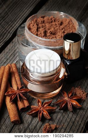 Chocolate skin treatment on wooden background. Cosmetic jar with lotion, cocoa, anise, cinnamon sticks, chocolate. Closeup