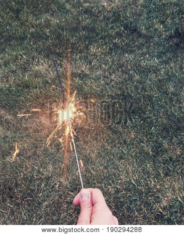 holding a forth of july firework sparkler on the grass in the summer