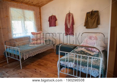 Old Slavic interior, bedroom with two beds, male and female clothes, and old box