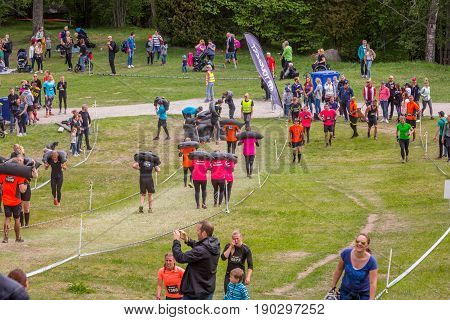 Stockholm Sweden - June 03 2017: View from above of a group of runners carry heavy sacks up a grass hill course to complete the annual event Toughest Stockholm. Many people in at the side and in the background.