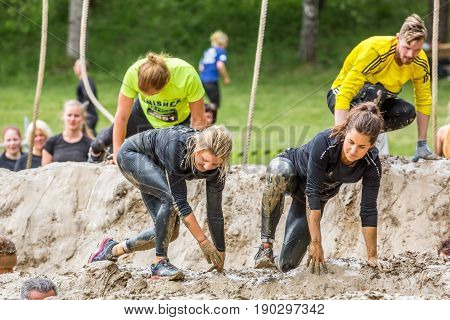 Stockholm Sweden - June 03 2017: Close up view caucasian women and men struggling in a mud obstacle to complete the course of the annual event Toughest Stockholm. People in the background.