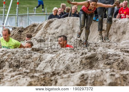 Stockholm Sweden - June 03 2017: Front view group of caucasian men an women in a mud obstacle struggling to complete the course of the annual event Toughest Stockholm.