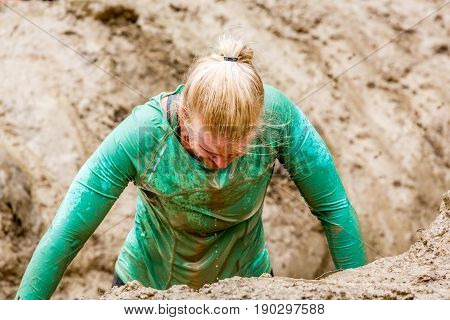 Stockholm Sweden - June 03 2017: Close up front view one caucasian woman struggling in a mud obstacle to complete the course of the annual event Toughest Stockholm.