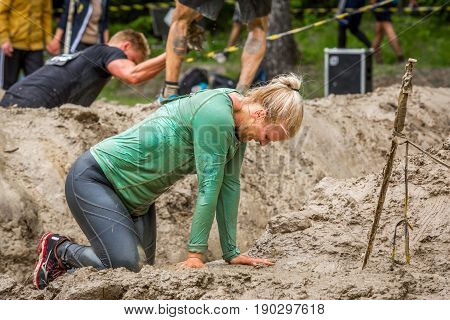 Stockholm Sweden - June 03 2017: Close up side view one exhausted caucasian woman in a mud obstacle to complete the course of the annual event Toughest Stockholm. People in the background.