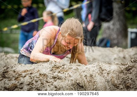 Stockholm Sweden - June 03 2017: Close up front view one caucasian woman struggling in a mud obstacle to complete the course of the annual event Toughest Stockholm. People in the background.