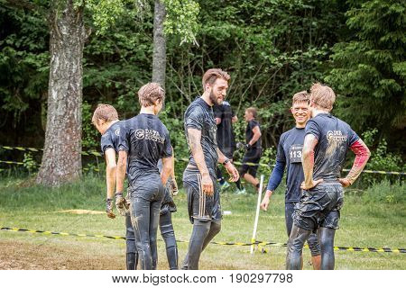Stockholm Sweden - June 03 2017: Rear view group of dirty caucasian male athletes talking and resting after completing a mud obstacle at the annual event Toughest Stockholm.