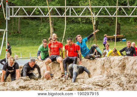 Stockholm Sweden - June 03 2017: Front view group of caucasian people struggling in an mud obstacle to complete the course of the annual event Toughest Stockholm.