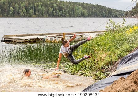 Stockholm Sweden - June 03 2017: Side view of caucasian woman in mid air after riding a water slide during the annual event Toughest Stockholm. One person laying in the water.