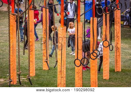 Stockholm Sweden - June 03 2017: Close up of an orange obstacle rig outdoors used in the annual event Toughest Stockholm. Adults and children seen in the background.