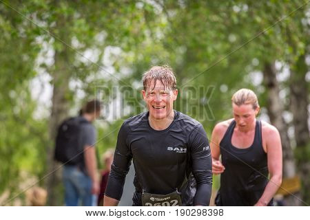 Stockholm Sweden - June 03 2017: Front view close up of two tired caucasian runners male and female after reaching the finish line in the annual event Toughest Stockholm. Blurred people in the background.