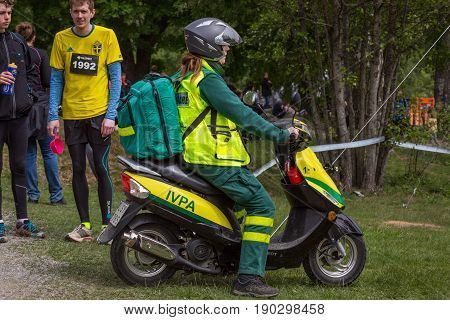 Stockholm Sweden - June 03 2017: Side view of one caucasian female paramedics on a motor scooter emergency vehicle on grass to assist in annual event Toughest Stockholm. Identifiable people next to the scooter.