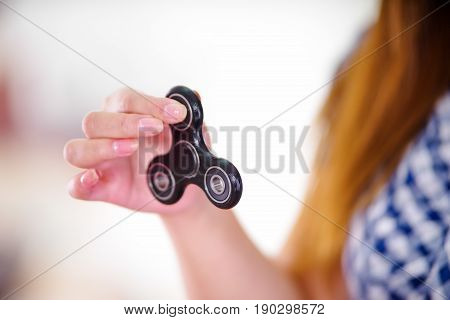 Young woman holding a popular fidget spinner toy in her hand.