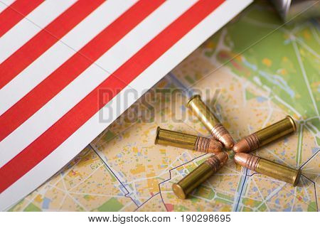 Close up of five bullets with a United States flag on a map, on wooden table.