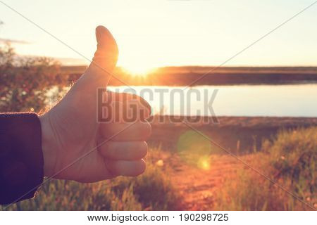 A man's hand holds a thumb up on background of bright sunrise. The concept of success and happiness. Everything will be fine.