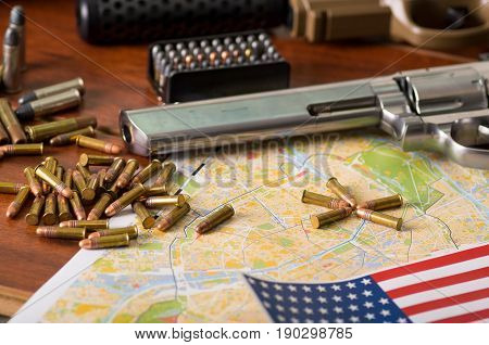 Close up of a shotgun and a revolver, cartridge belt with bullets with a blurred United States flag on a map, on wooden table.