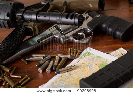 Bullets and a firearm. Bullets are a projectile expelled from the barrel of a firearm over a map, on wooden table.