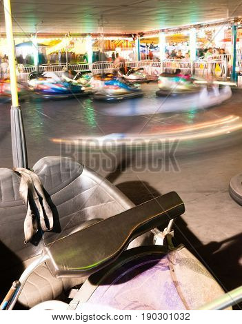 One sits unused while other bumper cars whirl around the track
