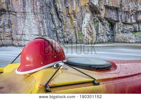 whitewater kayaking helmet on a kayak deck against river rapid and cliff