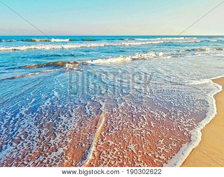 Beautiful beach ocean waves with sea foam.