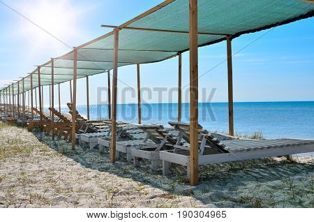 Wooden Sunbeds On The Background Of Blue Sea. Resorts, Vacation And Seascapes.