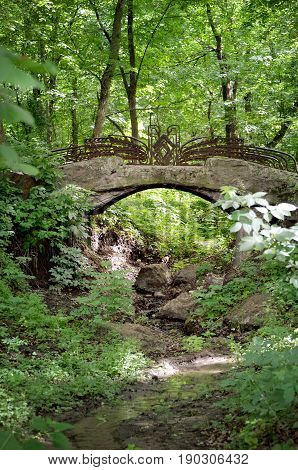 Summertime landscape with old stone bridge in the green forest