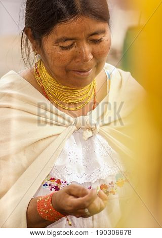 OTAVALO, ECUADOR - MAY 17, 2017: Close up of an unidentified hispanic indigenous woman wearing andean traditional clothing and necklace, posing for camera.