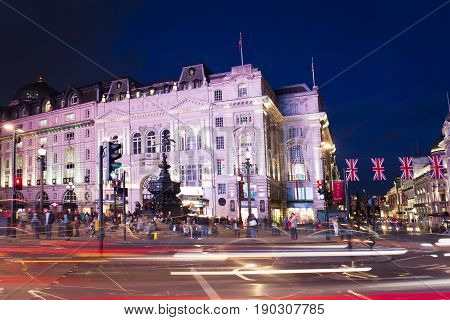 London, England, United Kingdom: 16 June 2017 - Popular tourist Picadilly circus with flags union jack in night lights illumination