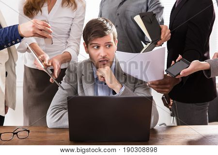 Scared Young Businessman Surrounded By Hands That Give Him A Lot Of Work In Office