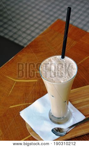 Frappe coffee with ice on a glass on a restaurant table