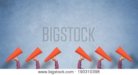 Close of woman making announcement in paper trumpet