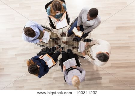 Elevated View Of People Sitting On Chair In Circle Reading Books
