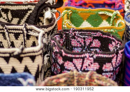 OTAVALO, ECUADOR - MAY 17, 2017: Beautiful andean traditional purse clothing textile yarn and woven by hand in wool, colorful fabrics background.