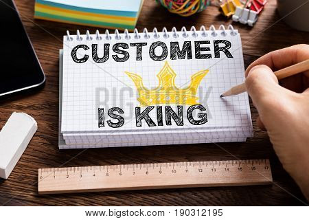 Close-up Of A Person Drawing Customer Is King Chart On Note Book Over The Desk