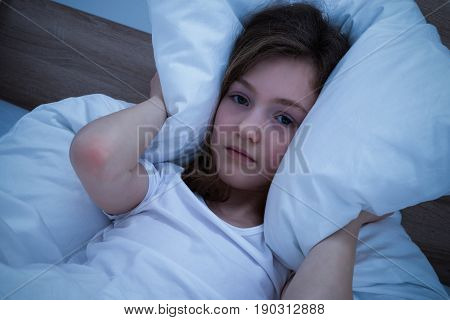 Cute Girl Lying In Bed Suffering From Sound Covering Her Ears With Pillow