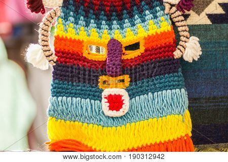 OTAVALO, ECUADOR - MAY 17, 2017: Beautiful andean traditional hat textile yarn and woven by hand in wool, usually people use for the diablada, colorful fabrics background.