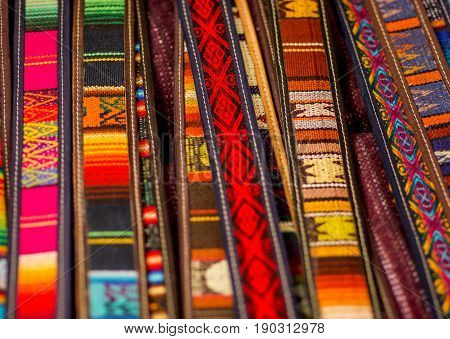 OTAVALO, ECUADOR - MAY 17, 2017: Beautiful andean traditional belt textile yarn and woven by hand in wool, colorful fabrics background.