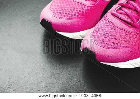 Pink sneakers on black background. Concept of healthy life, everyday training and force of will.