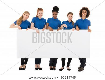 Group Of Smiling Female Janitors Holding Billboard In Front Of White Background