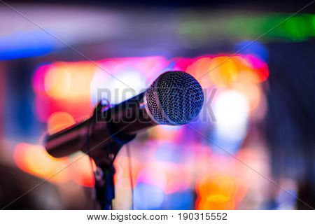 Microphone stands on stage in a nightclub. Bright club light shines on MIC. Performances in the night club