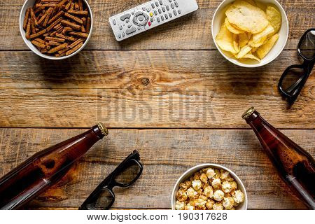 TV remote control, snacks, beer for whatchig film on wooden desk background top view space for text