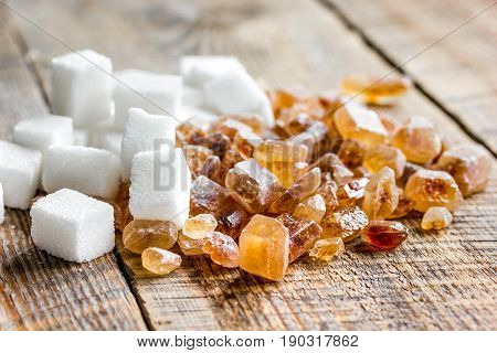 variety of sugar lumps on wooden kitchen table background