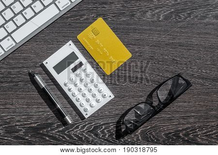 business purchasing with credit cards, keyboard and glasses on banker work desk dark background top view